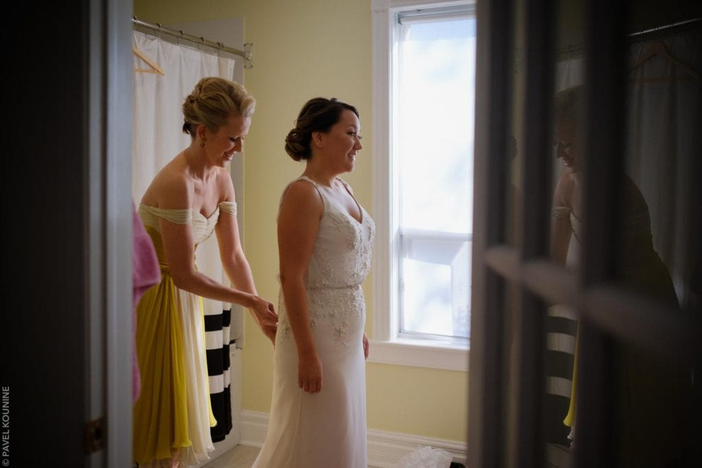 Timeless wedding photography of bride with maid of honour helping with the wedding dress.