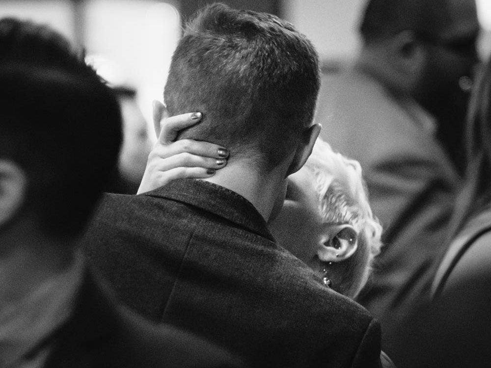 woman kissing man, backs turned to camera - wedding photography review