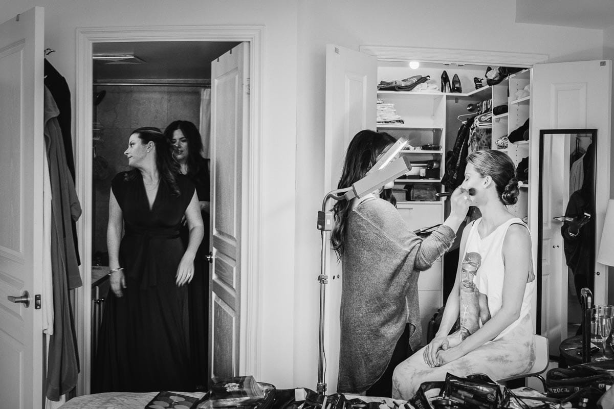 A woman checks her dress out in the ensuite bathroom while the bride is being made up in the bedroom.