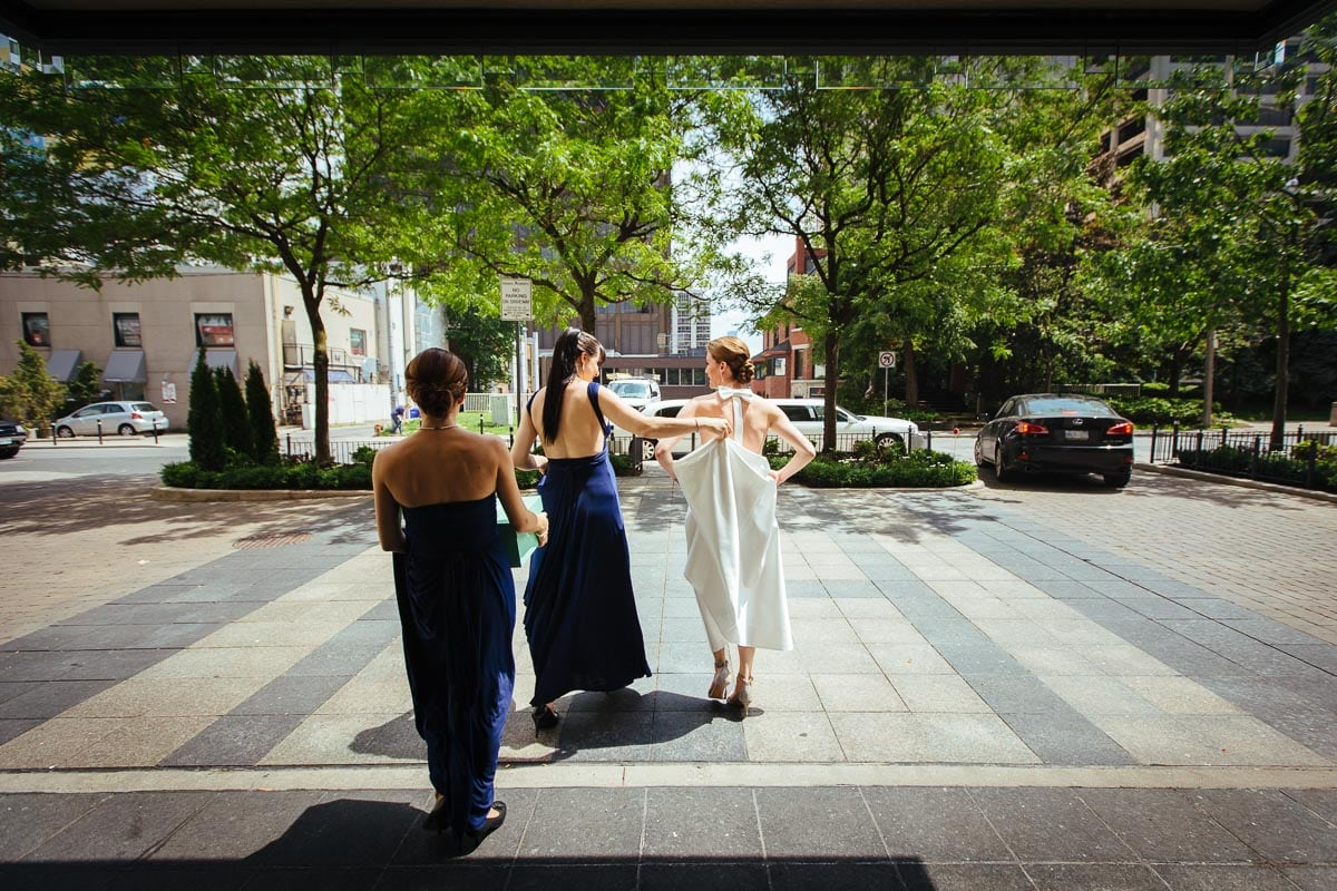 Bride and two bridesmaids walk towards limo.