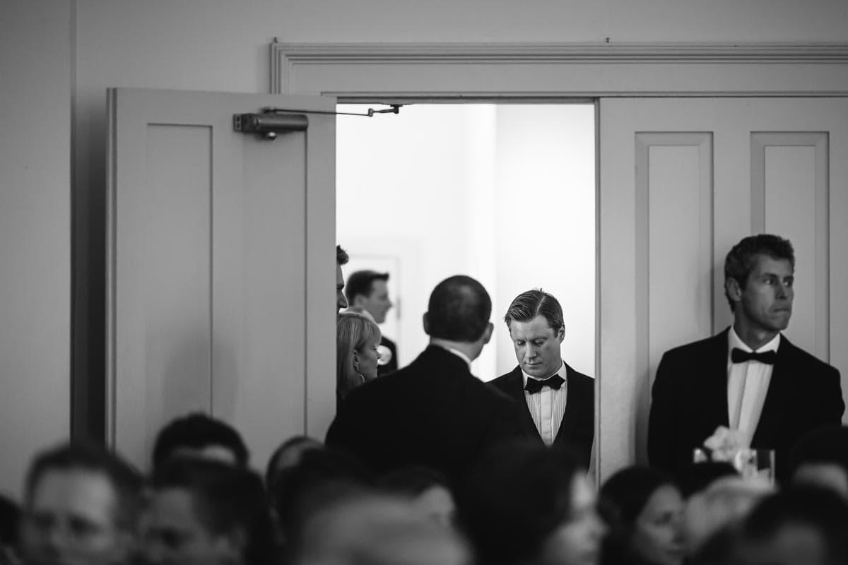 The groom and several groomsmen wait in the doorway of Enoch Turner Schoolhouse.