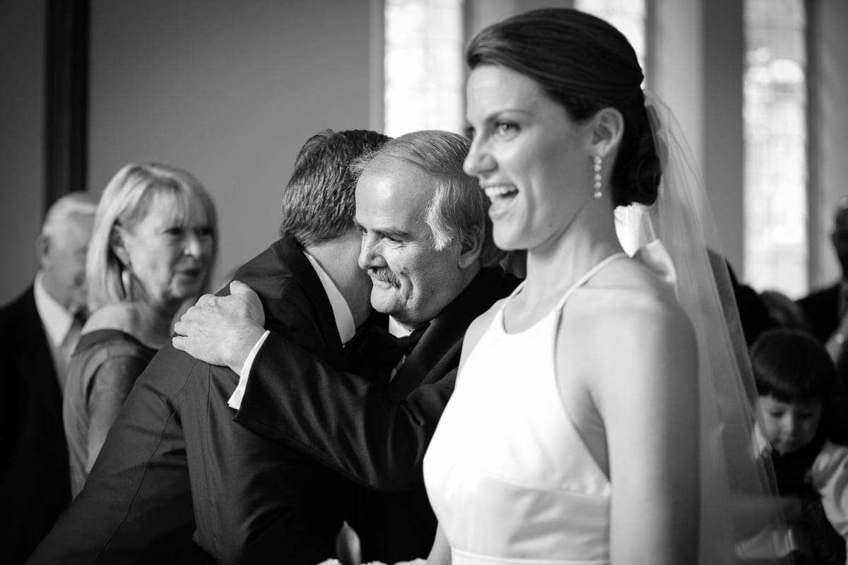 The bride smiles as her father hugs the groom at the top of the aisle at Enoch Turner Schoolhouse wedding.