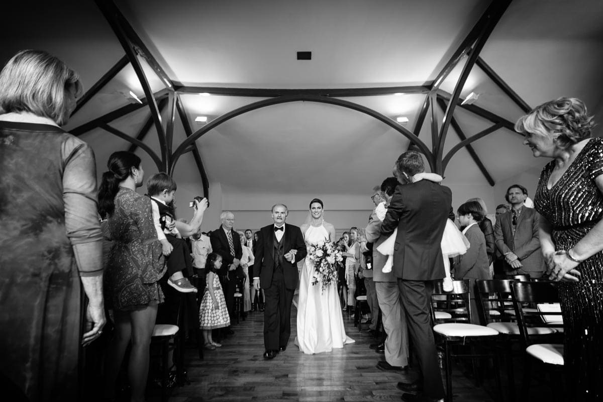 The bride and her father walk down the aisle for the wedding ceremony at Enoch Turner Schoolhouse.