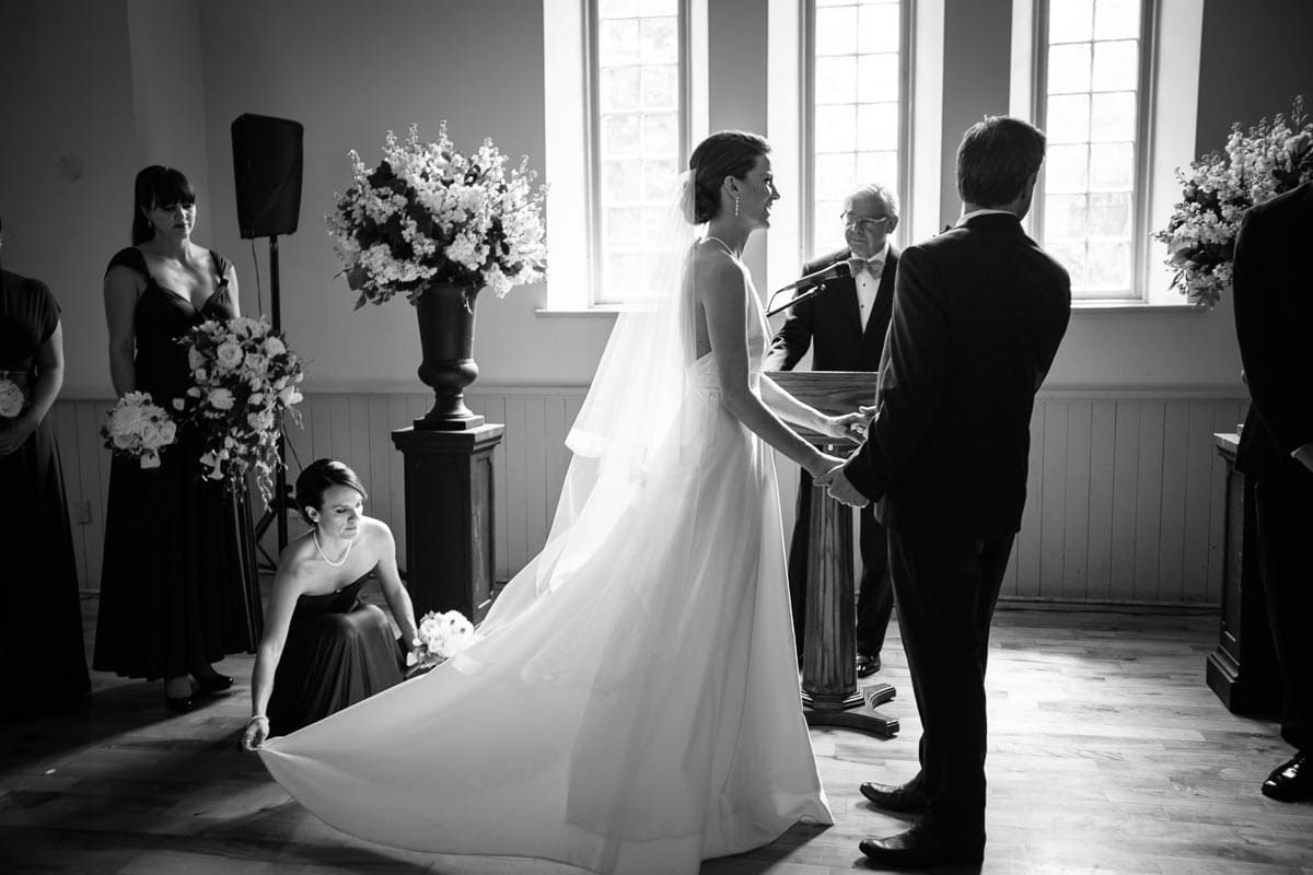 The maid of honour helps straighten out the bride's wedding gown as the bride and groom stand with the wedding officiant at Enoch Turner Schoolhouse.