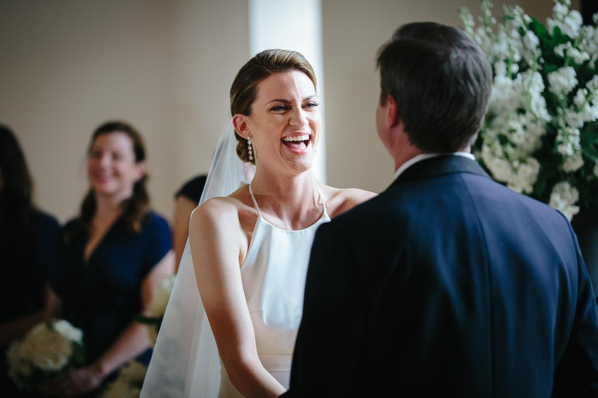 The bride laughs at the wedding officiant's joke while holding the groom's hands.
