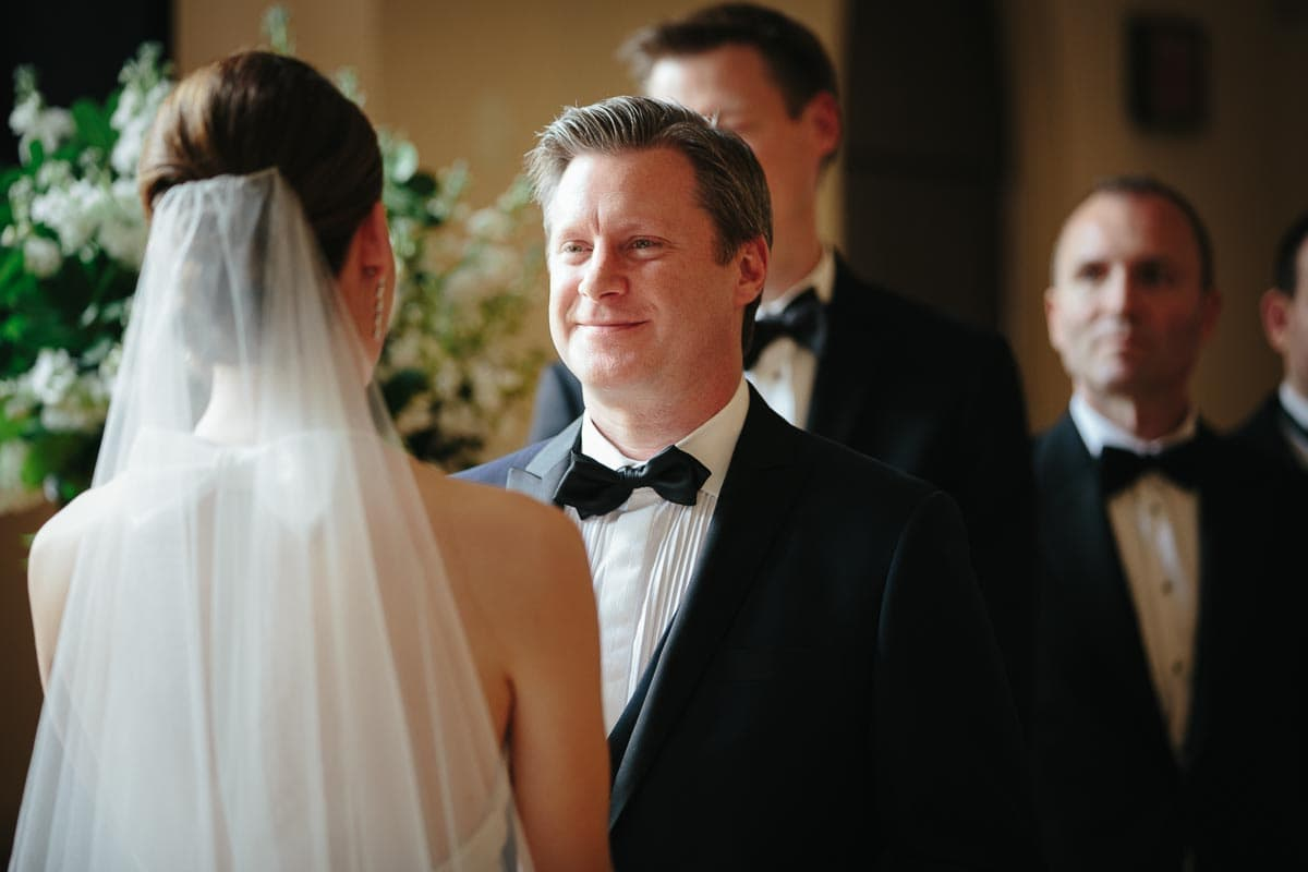 The groom smiles at the bride at Enoch Turner Schoolhouse wedding ceremony.