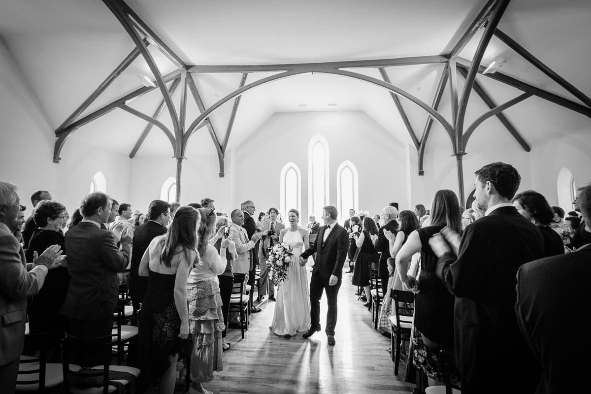 Bride and groom walk away after completing the wedding ceremony at Enoch Turner Schoolhouse.
