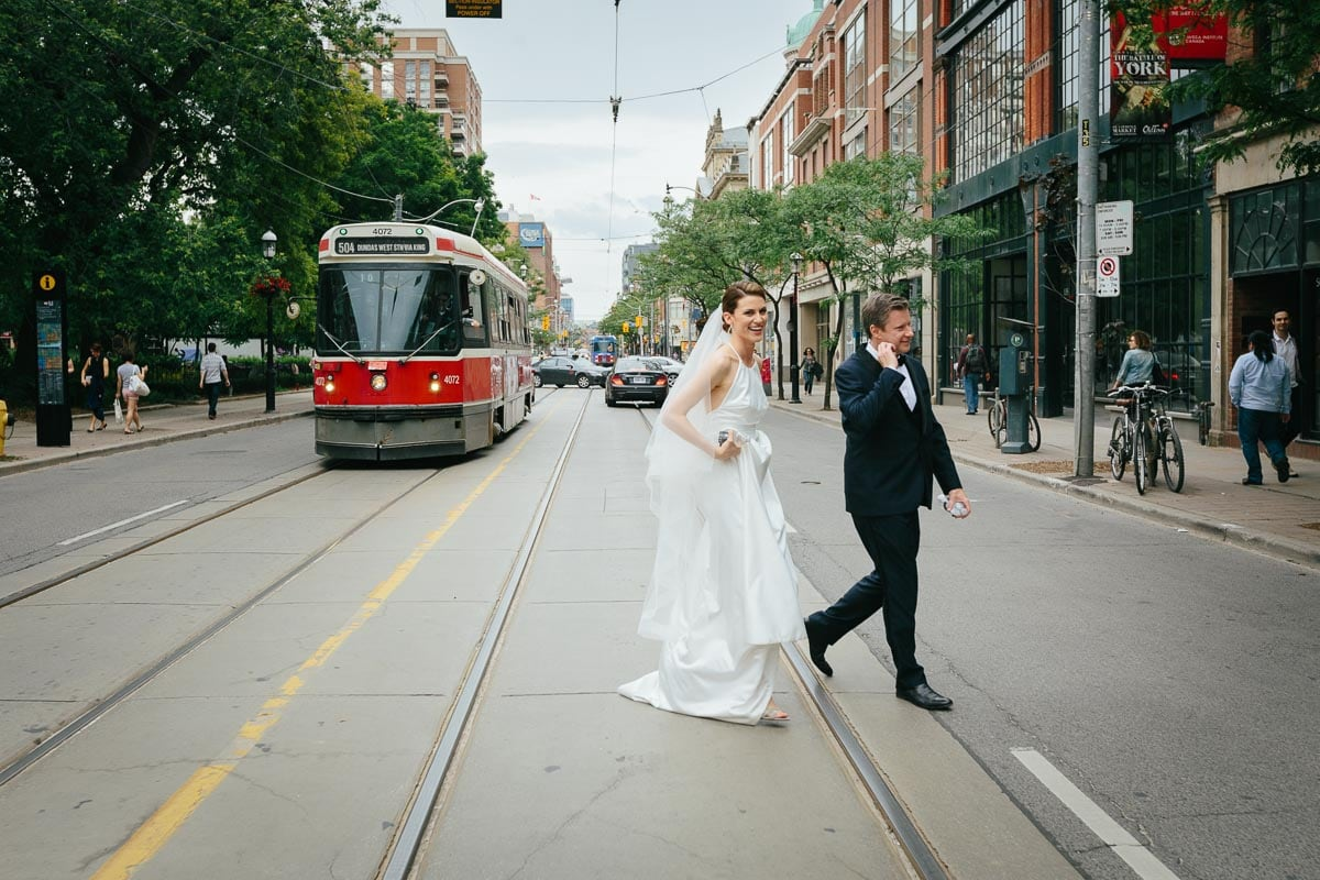 The bride and groom cross King Street East towards La Maquette restaurant. There is a TTC streetcar to the left of them.