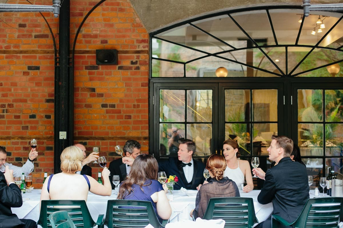 The wedding party, bride and groom, toast each other on the patio of La Maquette restaurant.