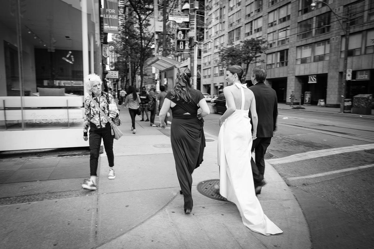 An old woman gives the bride and groom a dirty look as they cross the street to walk between restaurants.