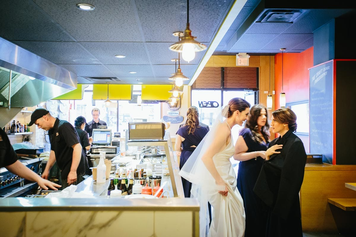 The bride is excited by something the bridesmaid said. They are standing near the counter of a gourmet hotdog restaurant.