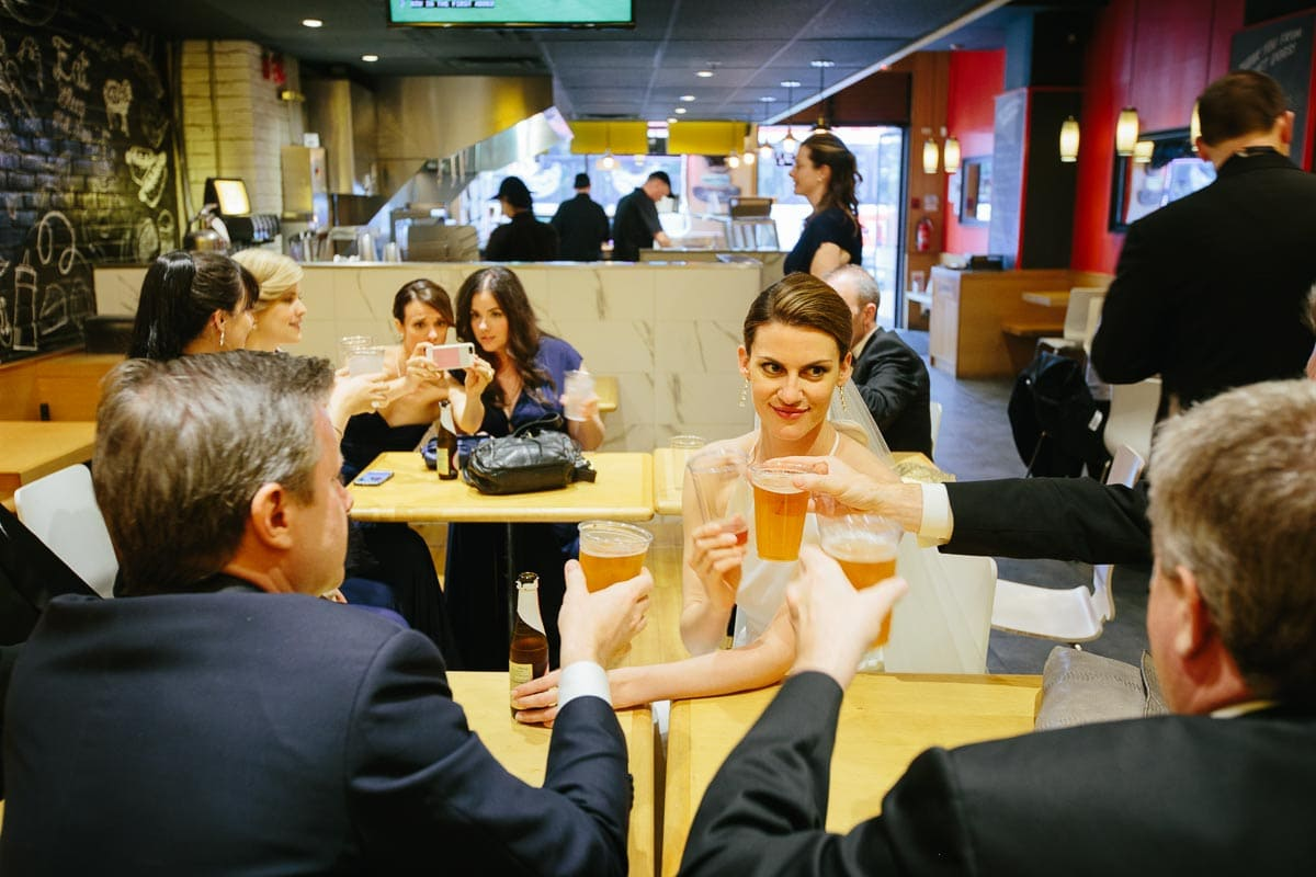 The bride and groomsmen toast their beer cups inside a gourmet hotdog restaurant. The bridesmaids sit at a different table looking at a mobile phone.