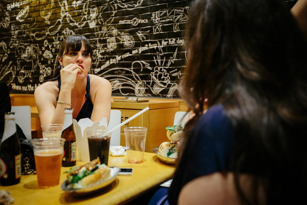 One of the bridesmaids is eating fast food at a table in a gourmet hotdog restaurant.