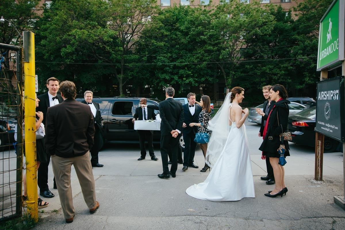 The bride, groom, and several guests converse in a loose group at the foot of the driveway to Airship 37.