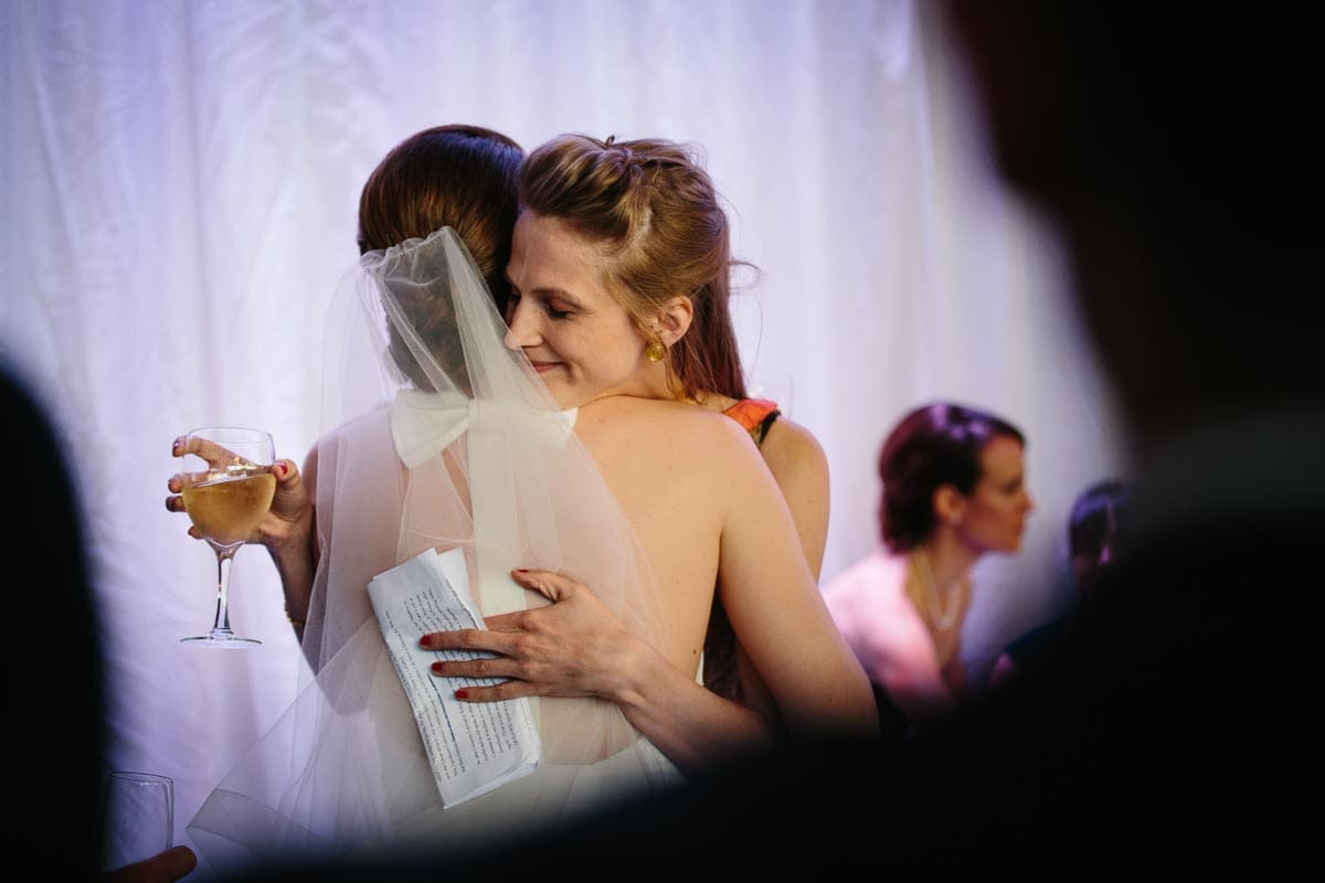 The bride is hugged by a guest who has just delivered a quick wedding speech at Airship37.