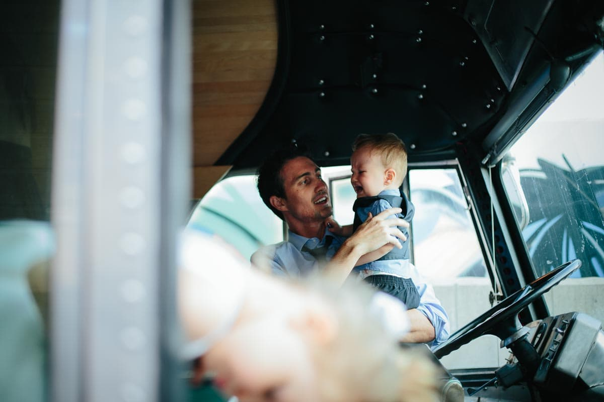 A man holds up a baby inside the RV on the patio of Airship37 during cocktail reception.