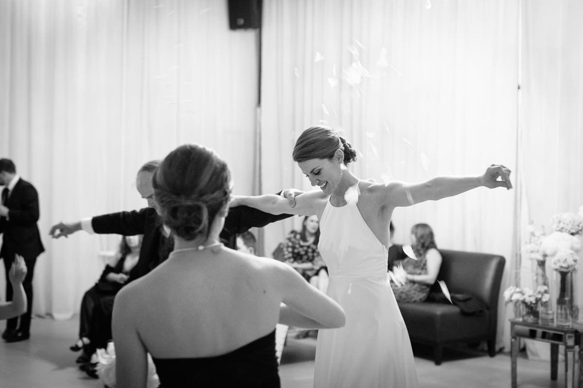 The bride's sister throws flower petals during the Father-Daughter dance at Airship37 wedding.