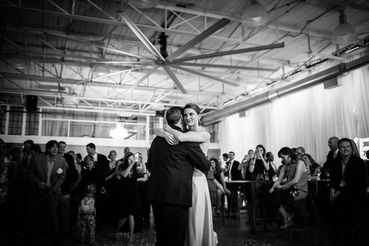 The bride and groom embrace as they slow dance beneath the Big Ass Fan at the Airship37 wedding reception.