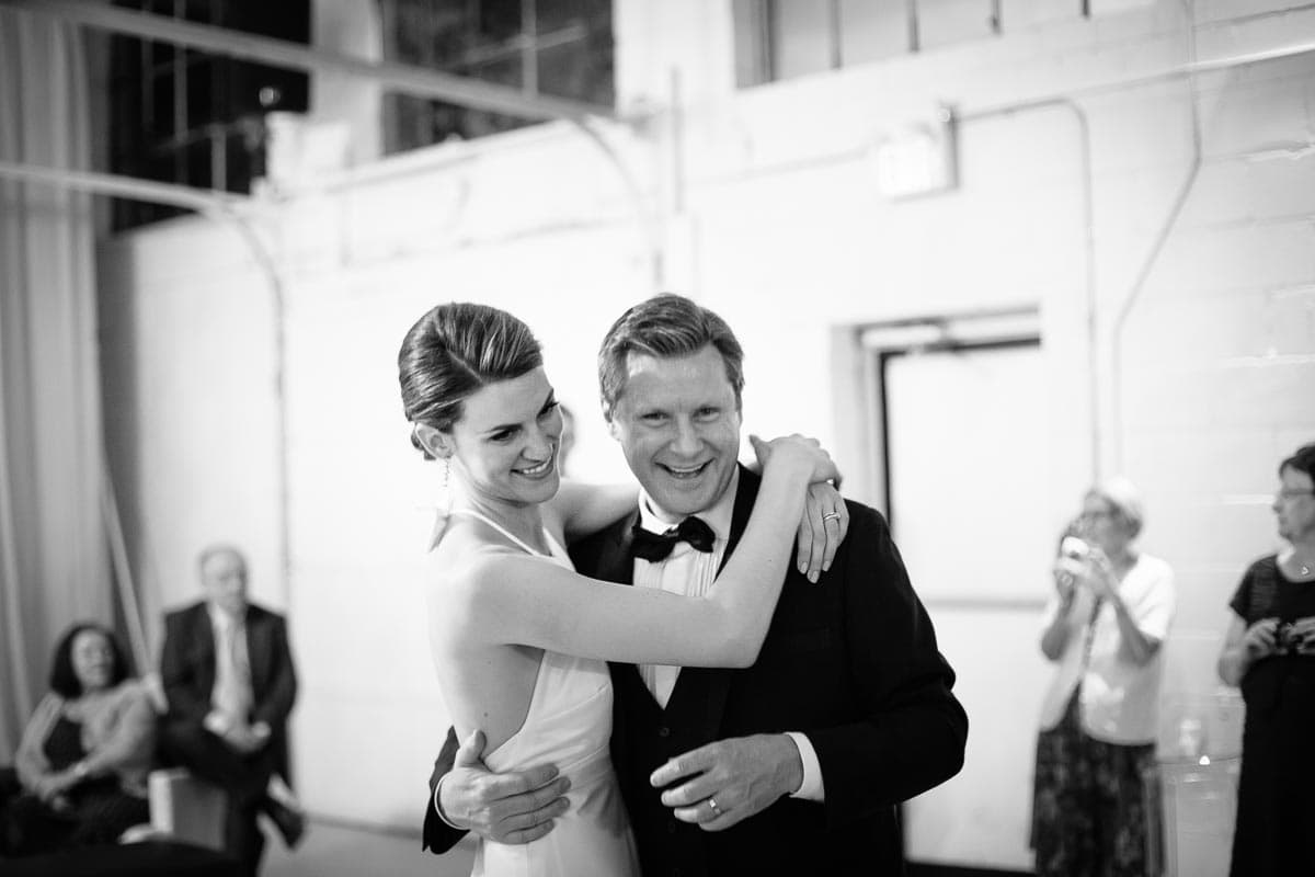 The bride and groom embrace and laugh after completing their dance at this Airship37 wedding reception.