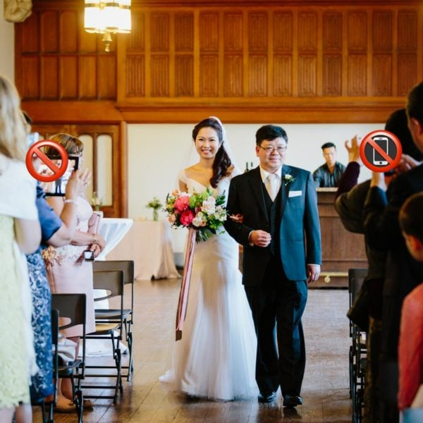 Guests take photos using mobile phones and tablets as bride walks down the aisle with her father in this not unplugged wedding.