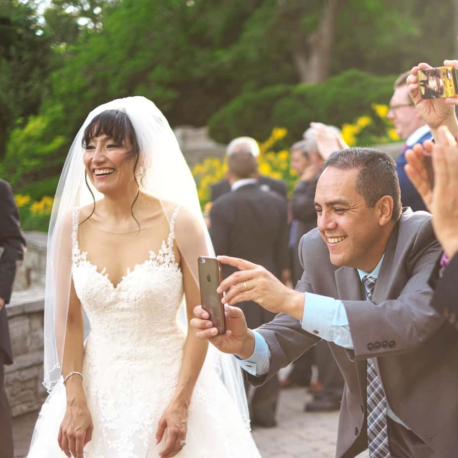 Bride smiling as wedding guests take photos with their phones.