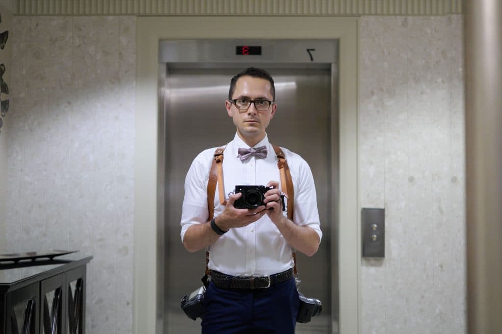 What do wedding photographers wear? A wedding photographer wearing white dress shirt, bowtie, and navy trousers.