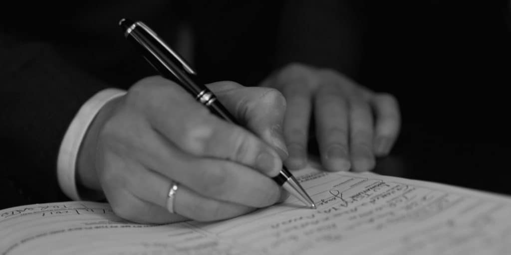 Closeup of male hands signing a wedding photography contract with pen.