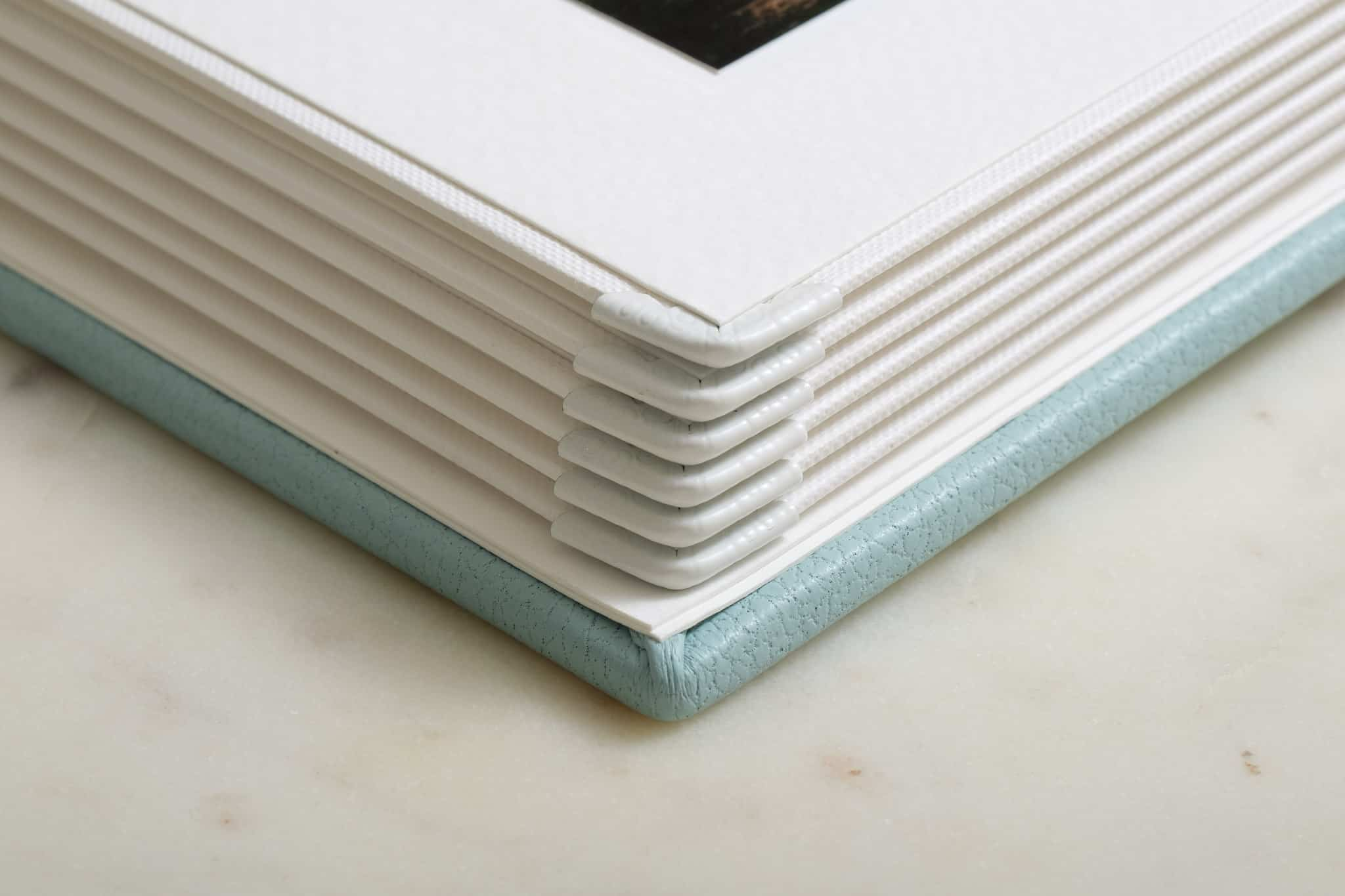 Pagement matted wedding photo albums with corner protectors.
